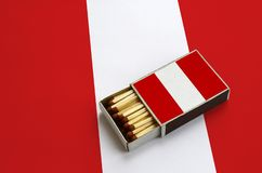 Peru flag is shown in an open matchbox, which is filled with matches and lies on a large flag.  royalty free stock images