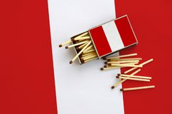 Peru flag is shown on an open matchbox, from which several matches fall and lies on a large flag.  stock images