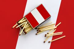 Peru flag is shown on an open matchbox, from which several matches fall and lies on a large flag.  stock photos