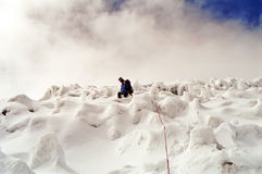 Peru Mountain Climb. A mountaineer attached to a rope climbing a glacial covered mountain with clouds above stock photos