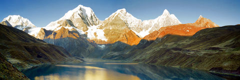 Peru Mountain Sunrise Panorama. The Huayhuash mountain range reflecting  in lake Carhuacocha at sunrise, Peru