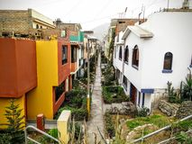 Peru Neighborhood. A simple path with houses down each side. Vivid colors and greenery surround the landscape. It is a very immersive picture of architecture Royalty Free Stock Photo