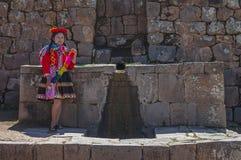 Peruanische einheimische Frau durch einen Brunnen, Cusco stockfotos