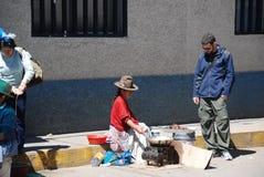 Peruanische Frau der Armut und ein Tourist lizenzfreie stockbilder