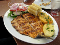 Peruanischer Teller - gebratenes Fischfilet mit Gemüse, Zwiebel, Mais, kochte Kartoffeln Lizenzfreies Stockbild