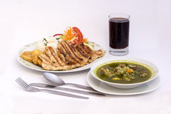 Peruanischer Teller: Hühnersuppe des Korianders, des morada Aguadito de Pollo) +chicha (purpurroter Maissaft) und des Huhns gegri lizenzfreie stockfotografie