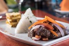 Peruanisches Lebensmittel lomo saltado: Ein gesalzenes Rindfleisch mit Tomaten, Zwiebel, briet Kartoffeln und Reis stockbild