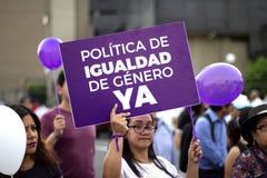 Peruanisches Mädchen, das purpurrote Fahne von 'Igualdad de Genero hält ' stockbilder
