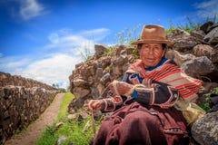 Peruansk indisk kvinna i traditionellt väva för klänning Arkivfoto