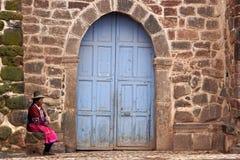 Peruansk kvinna som framme sitter av kyrkan i San Pablo Arkivbild