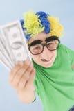 A peruca desgastando e a falsificação do palhaço do menino cheiram o dinheiro da terra arrendada Imagem de Stock