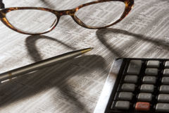 Perusing the stock market. Paper, glasses, pen, and calculator, items showing someone looking over stocks Royalty Free Stock Image
