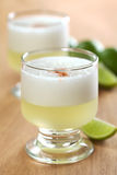Peruvian Cocktail Called Pisco Sour. Made of Pisco (Peruvian grape schnaps), lime juice, syrup and egg white (Selective Focus, Focus on the front glass rim Royalty Free Stock Photography