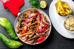 Peruvian dish Lomo saltado - beef tenderloin with purple onion, yellow chili, tomatoes in pan. Tot view. Peruvian dish Lomo saltado - beef tenderloin with purple Stock Images
