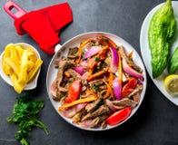Peruvian dish Lomo saltado - beef tenderloin with purple onion, yellow chili, tomatoes in pan. Tot view. Peruvian dish Lomo saltado - beef tenderloin with purple Stock Image