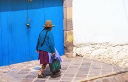 Peruvian elderly woman in traditional dress on the street of Cusco, Peru, Latin America. horizontal, brown hat. Blue door, selective focus royalty free stock photo