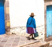 Peruvian elderly woman in traditional dress on the street of Cusco, Peru, Latin America. horizontal, brown hat. Blue door, selective focus stock photography