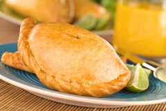 Peruvian Empanada. Peruvian snack called Empanada (pie) filled with chicken and beef served with limes (Selective Focus, Focus on the middle front part of the Royalty Free Stock Images