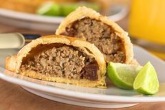 Peruvian Empanada. Peruvian snack called Empanada (pie) filled with beef and raisin served with limes (Selective Focus, Focus on the empanada stuffing in the Royalty Free Stock Photos