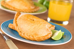 Peruvian Empanada Meat Filled Pastries. Peruvian snack called Empanada (pie) filled with chicken and beef meat on blue plate with limes (Selective Focus, Focus Stock Photo