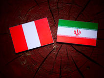 Peruvian flag with Iranian flag on a tree stump isolated Royalty Free Stock Photography