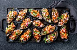 PERUVIAN FOOD. Choros a la chalaca. Big mussels, choros zapatos seasoned with purple onion, tomatoes, corn and lemon. Top view, black background. Traditional royalty free stock photography