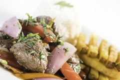 Peruvian food `lomo saltado`. Peruvian food lomo saltado :A salted beef with tomatoes, onion, fried potatoes and rice Royalty Free Stock Image