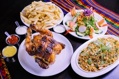 Peruvian food: Pollo a la brasa con arroz chaufa. Peruvian food traditional of peru. Grilled chicken with french fries and salad with arroz chaufa royalty free stock images