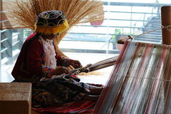 Peruvian indigenous woman is weaving a carpet. Royalty Free Stock Photos