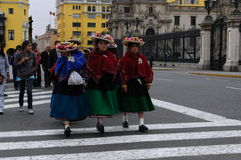 Peruvian indigenous women are crossing the street near the Government palace in Lima, Peru. stock images
