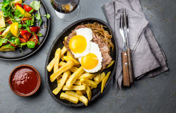 Peruvian Latin American food. Lomo a lo pobre. Beef whit fried potatoes french fry and eggs. served with salad. Top view Stock Photos