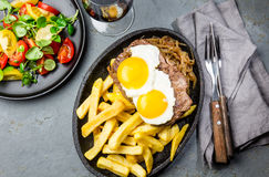 Peruvian Latin American food. Lomo a lo pobre. Beef whit fried potatoes french fry and eggs. served with salad. Top view Royalty Free Stock Photos