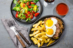 Peruvian Latin American food. Lomo a lo pobre. Beef whit fried potatoes french fry and eggs. served with salad. Top view Royalty Free Stock Image
