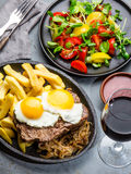 Peruvian Latin American food. Lomo a lo pobre. Beef whit fried potatoes french fry and eggs. served with salad. Top view Stock Photography