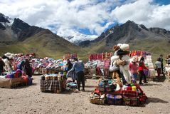 Peruvian market in the highlands. A Peruvian market with colorful textiles, blankets, hats, yarn and other goods, with snow-capped mountains in the background Stock Photos