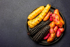 Peruvian raw ingredients for cooking black corn and sweet potatoes. Top view Royalty Free Stock Photos