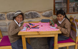 Peruvian School Children. Happy Peruvian school girls sitting outdoors in Ollantaytambo March 13,2013 Royalty Free Stock Images