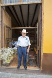 Peruvian senior in front of bar in Trujilo historic center. TRUJILLO, PERU, JANUARY 24: Unidentified man standing outside a bar and wearing a Peruvian hat in stock photography