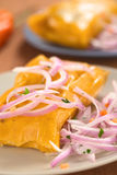 Peruvian Tamales. (traditionally eaten for breakfast on Sundays) made of corn and chicken and served with salsa criolla (onion salad) (Selective Focus, Focus on stock images