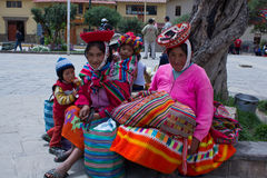 Peruvian women and children. Portrait of women and children dressed in traditional clothing sitting in the busy Central Plaza of Ollantaytambo Peru March 13 Stock Photos