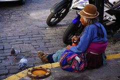 Peruvian Woman. A homeless Peruvian woman in traditional clothing with some pigeons in Arequipa Stock Images