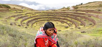 Peruvian woman and Moray inca ruins. Picture of Peruvian woman in native costume of red yellow and black with the Moray inca ruins in the background, a stock photos