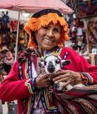 Peruvian Woman With a Baby Llama. A Peruvian woman posing for a photo with a baby llama in the Andes Mountains of Peru stock photo