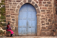 Peruvian woman sitting in front of the church in San Pablo Stock Photography