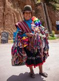 Peruvian Woman Selling Souvenirs. A Peruvian woman, in traditional attire, selling souvenirs in the Andes Mountains of Peru royalty free stock photography