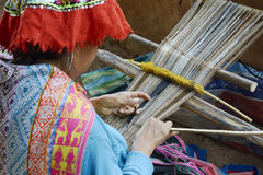 Peruvian woman in traditional clothing weaving cloth on a loom Stock Images