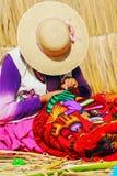 Peruvian women knitting traditional handmade craft in Uros Island, Puno, Peru stock photo