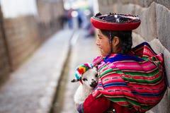 Peruviano indigeno che tiene un agnello del bambino Immagini Stock