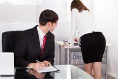 Pervert businessman looking at businesswoman Stock Photography