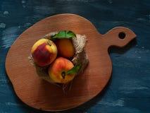 Perziken in jute op een houten raad op een blauwe achtergrond, vrije ruimte voor tekst Royalty-vrije Stock Foto